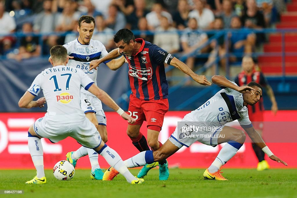 Caen's French midfielder Julien Feret vies for the ball with Bastia's French defender Mathieu Peybernes Bastia's French defender Sebastien Squillaci...