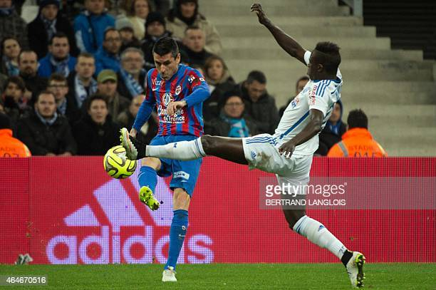 Caen's French midfielder Julien Feret vies with Marseille's French defender Benjamin Mendy during the French L1 football match OM vs Caen on February...