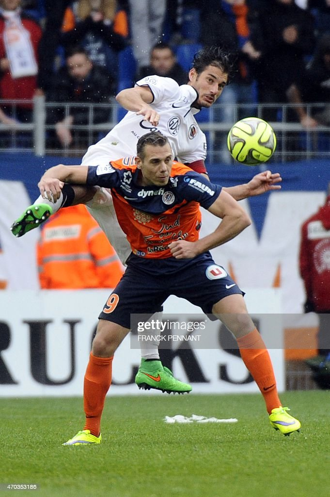 Caen's French midfielder Nicolas Seube (up) vies with Montpellier's French forward Kevin Berigaud during the French L1 football match between Montpellier and Caen at Mosson Stadium in Montpellier, southern France, on April 19, 2015. AFP PHOTO / FRANCK PENNANT