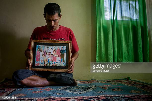 Café owner Amirizal points to a photograph of his family before the tsunami which took nine of his eleven brothers and leaving him with only one leg...