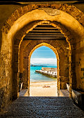 Archway through an ancient stone building leading to a beach with unrecognizable people in Cefalu, Sicily, Italy