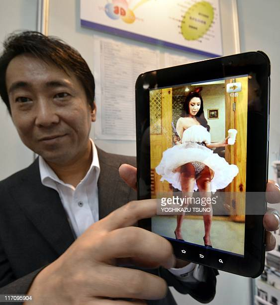 A Cafe Digital employee displays a tablet with touch sensor featuring a woman flapping her skirt during the annual virtual reality expo in Tokyo on...