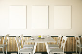 Cafe interior with cake on table and three blank posters on light wall. Mock up, 3D Rendering