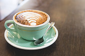 coffee on wooden table with vintage cup, saucer and spoon