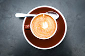 A single cafe macchiato ready to be enjoyed on a gray table. Top down image with copy space.