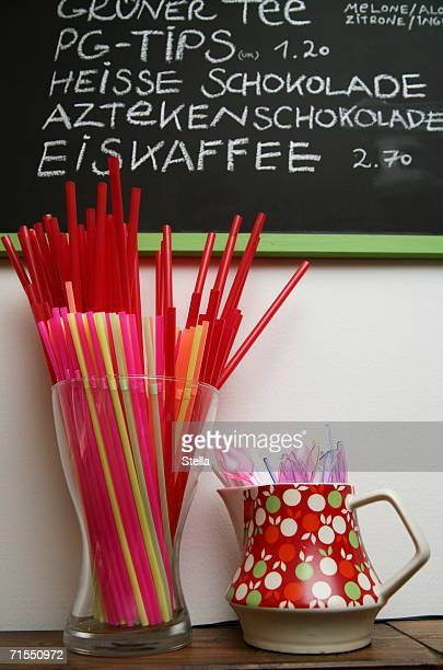 Cafe menu board with plastic spoons and straws below