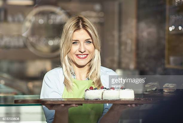 Cafe Owner Looking at Camera and Holding Sweet Food