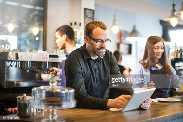 cafe owner updating  social media with a digital tablet