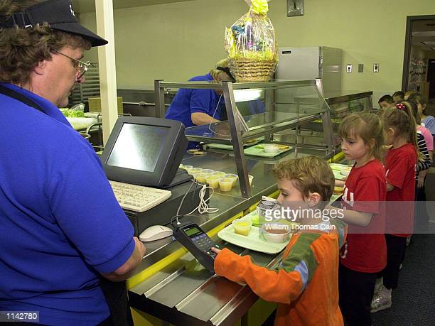 Cafeteria cashier Cathy Kelly helps 1stgrader Joel Ritchey use the fingerprint scanner to pay for lunch at Penn Cambria PrePrimary School March 1...