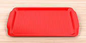 Empty red plastic tray on wood table