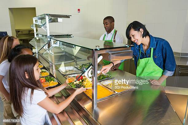Cafeteria worker serving healthy food to children in lunch line
