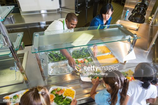Cafeteria worker serving trays of healthy food to children
