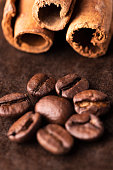 Caffee beand with cinnamon on brown background