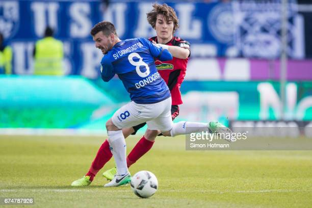 Caglar Soeyuencue of Freiburg is challenged by Jerome Gondorf of Darmstadt during the Bundesliga match between SV Darmstadt 98 and SC Freiburg at...