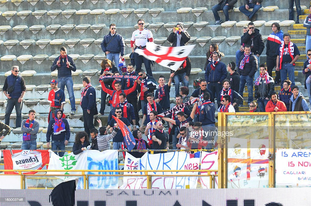 Cagliari Calcio fans hold their team scarves aloft as they show their support during the Serie A match between Bologna FC and Cagliari Calcio at Stadio Renato Dall'Ara on March 3, 2013 in Bologna, Italy.