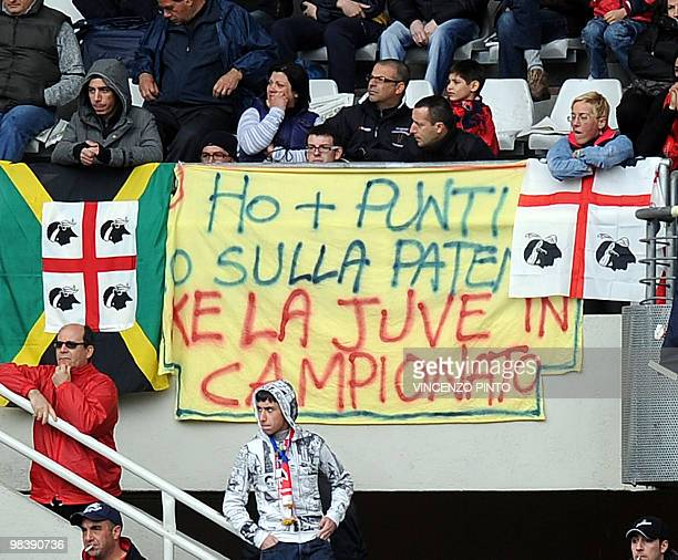 Cagliari supporters shows a banner reading ' I have more points on my driver license than Juventus in the championship' during the Serie A football...