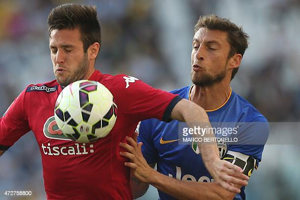 Cagliari's Croatian forward Duje Cop fights for the ball with Juventus' midfielder Claudio Marchisio during the Italian Serie A football match...