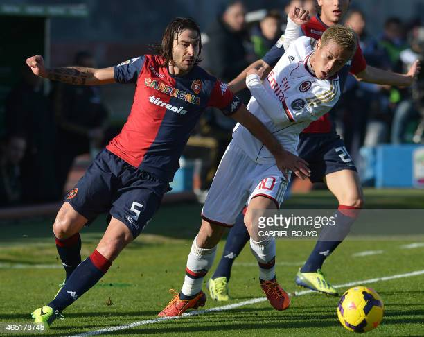 Cagliari's midfielder Daniele Conti vies with AC Milan's Japanese midfielder Keisuke Honda during the Italian Serie A football match between Cagliari...