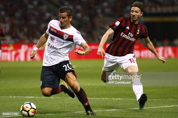 Cagliari's midfielder Simone Padoin fights for the ball with AC Milan's midfielder Riccardo Montolivo during the Italian Serie A football match AC...