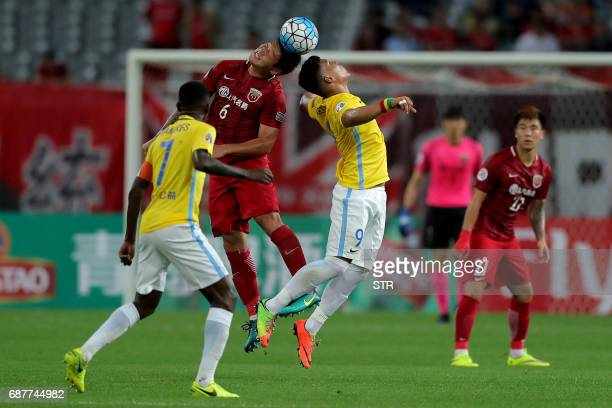 Cai Huikang of China's Shanghai SIPG fights for the ball with Roger Beyker Martinez of China's Jiangsu FC during their AFC Champions League round of...
