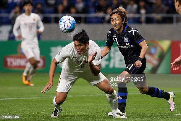 Cai Huikang of Shanghai SIPG and Shu Kurata of Gamba Osaka compete for the ball during the AFC Champions League Group G match between Gamba Osaka and...