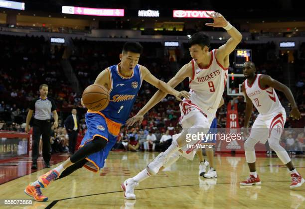 Cai Liang of Shanghai Sharks drives the ball to the basket defended by Zhou Qi of Houston Rockets in the second half at Toyota Center on October 5...