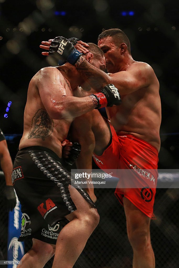 Cain Velasquez (R) receives a knee hit from Fabricio Werdum (L) during a UFC Heavyweight Championship Fight between Cain Velasquez and Fabricio Werdum at Arena Ciudad de Mexico on June 13, 2015 in Mexico City, Mexico.