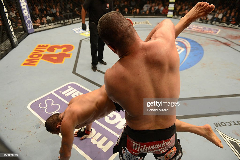 Cain Velasquez takes down Junior dos Santos during their heavyweight championship fight at UFC 155 on December 29, 2012 at MGM Grand Garden Arena in Las Vegas, Nevada.