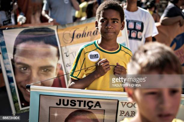 TOPSHOT Caique da Silva Martins holds a placard of his 13yearold brother killed two years ago by a stray bullet during a rally against violence...