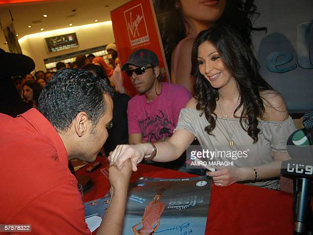 A fan kisses the hand of Lebanese pop singer Elissa during a press conference at the Virgin Megastore in Cairo 10 May 2006 AFP PHOTO/AMRO MARAGHI