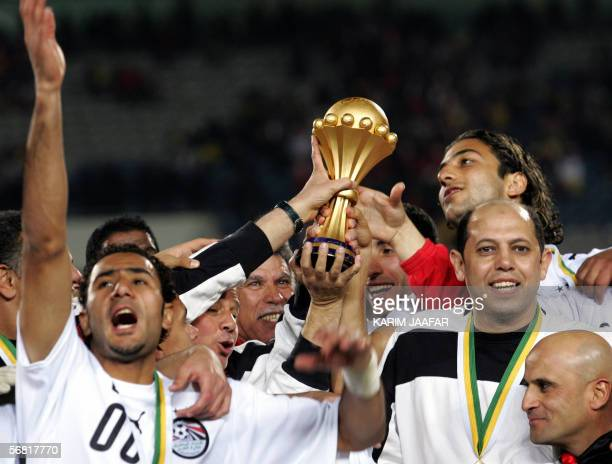 Egyptian forward Ahmed 'Mido' Hossam poses with teammates holding the trophy at the end of the African Nations Cup final football game at Cairo's...