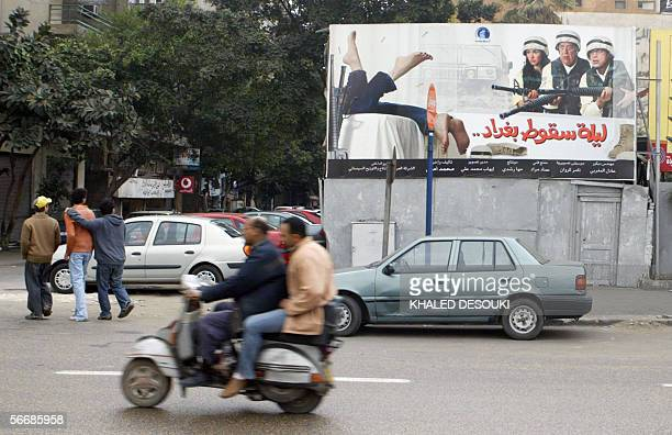 TO GO WITH AFP STORY BY JOELLE BASSOUL Egyptians ride a motorbike past a poster advertising the new Egyptian film 'The Night Baghdad Fell' 27 January...