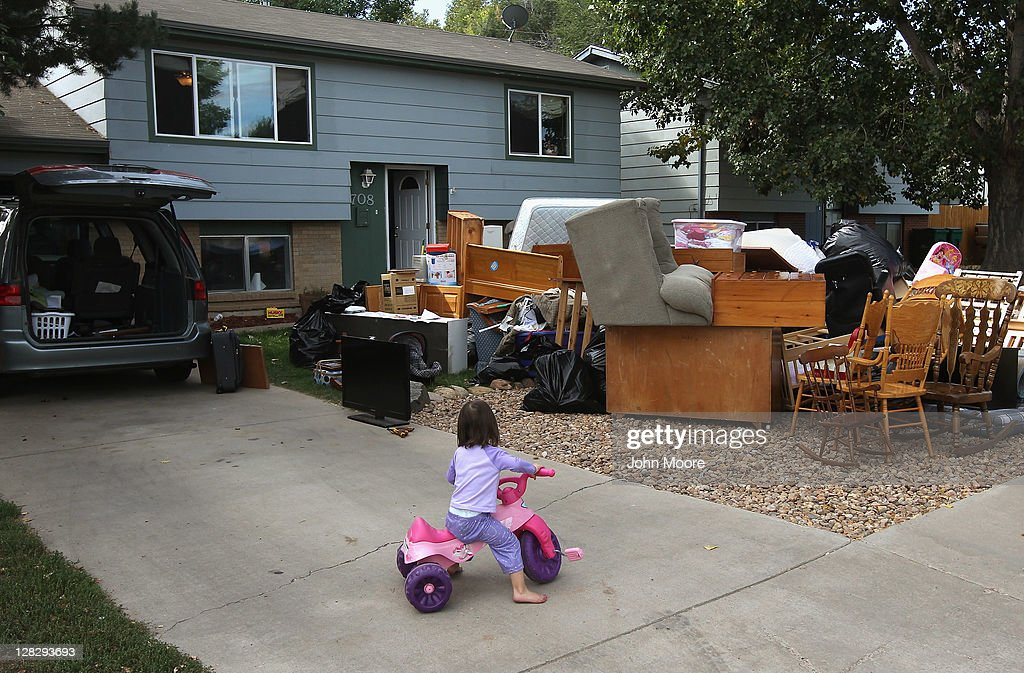 Caitlin Barbiere, 2 1/2, plays in the driveway as her family's possessions sit piled in the front yard during a home foreclosure eviction on October 5, 2011 in Milliken, Colorado. Her mother, Brandie Barbiere (L), said she had stopped making mortgage payments 11 months before, after she lost more than half her home child care business due to the continued weak economy. The Barbiere family possessions were removed to the front yard by an eviction team and the door locks changed. A nationwide glut of foreclosed homes is expected to depress U.S. housing values for years.