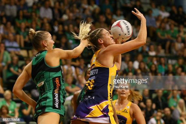 Caitlin Bassett of the Lightning receives a pass against Courtney Bruce of the Fever during the round six Super Netball match between the Fever and...
