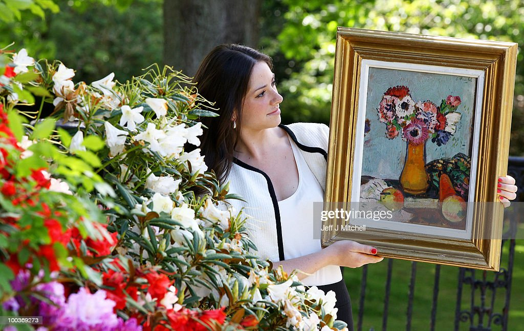 Caitlin Cruckshanks from Lyon & Turnbull holds a still life by Scottish Colourist George Leslie Hunter called Still Life with Fruit and Anemones at Pollock House on May 24, 2010 in Glasgow, Scotland. The painting now valued at £30,000 is one of a group of four Hunters discovered and acquired by the family�s father, a Glasgow auctioneer, in London in the late 1960's. He was himself a talented artist and friend of the artist J D Fergusson, and bought the paintings before the importance of Scottish Colourists was well recognised. One painting from the group was gifted to the City of Glasgow in his memory following his death in 1969 and is held in the City's Kelvingrove Collection. The 'Anenomes' painting is now being sold by his family following the death of his widow.
