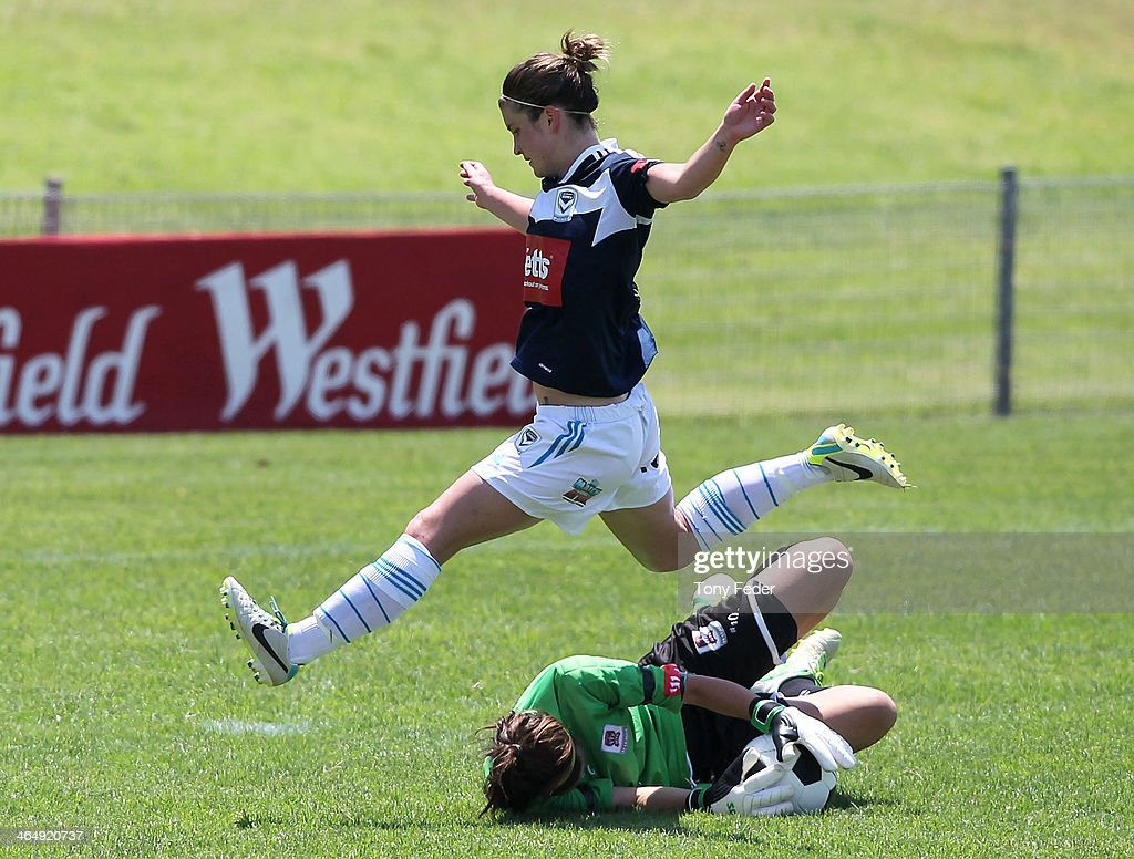 Caitlin Friend of the Victory leaps over the top of Jets goalkeeper Eliza Campbell during the round 10 W-League match between the Newcastle Jets and Melbourne Victory at Adamstown Oval on January 25, 2014 in Newcastle, Australia.