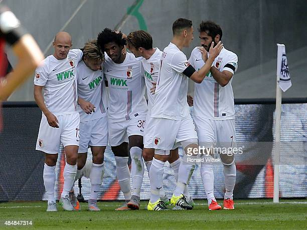 Caiuby of Augsburg celebrates after scoring his team's first goal with his teammates during the Bundesliga match between Eintracht Frankfurt and FC...
