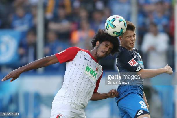 Caiuby of Augsburg fights for the ball with Dennis Geiger of Hoffenheim during the Bundesliga match between TSG 1899 Hoffenheim and FC Augsburg at...