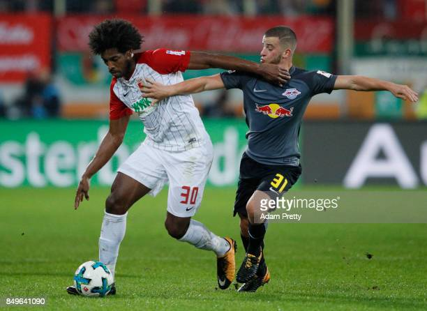 Caiuby of Augsburg fights for the ball with Diego Demme of Leipzig during the Bundesliga match between FC Augsburg and RB Leipzig at WWKArena on...