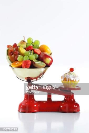 Cake and fruit on red scales : Stock Photo