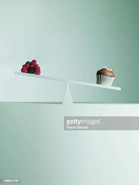 Cake cubes tipping seesaw with berries on opposite end