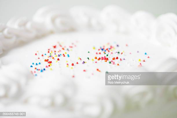 Cake decorated with icing and sprinkles (focus on sprinkles)