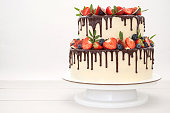 Two-tiered cake in chocolate, decorated with slices strawberries, blueberries, figs and green leaves on a white wooden table. Picture for a menu or a confectionery catalog.