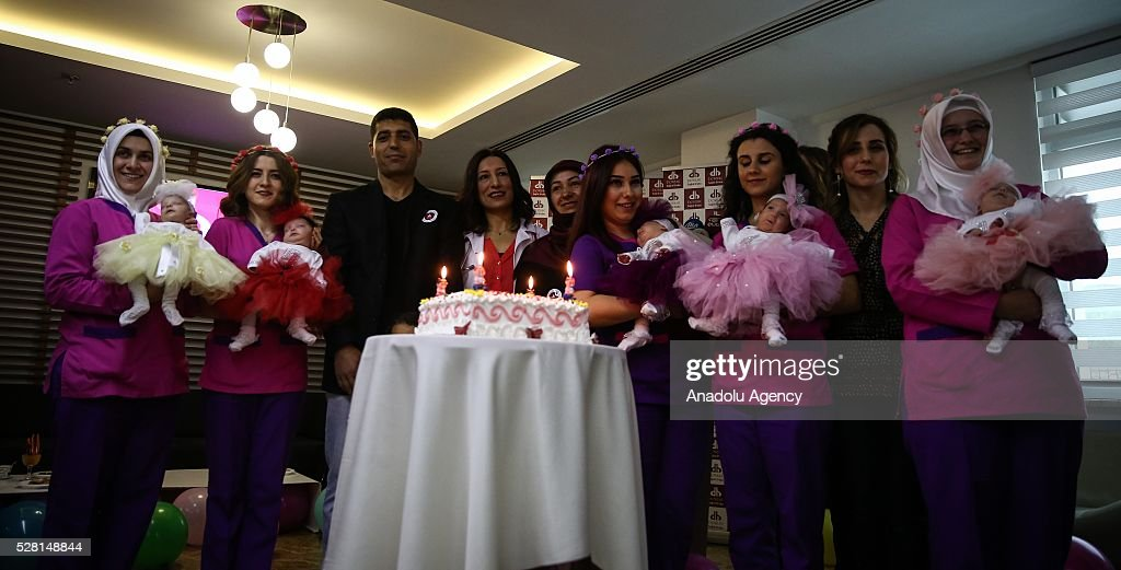 A cake is seen as women hold 83 days old quintuplet babies, who were born in the 28th week of the pregnancy, after the babies were discharged from the hospital in Bursa, Turkey on May 4, 2016. Quintuplets occur naturally in 1 in 55,000,000 births.