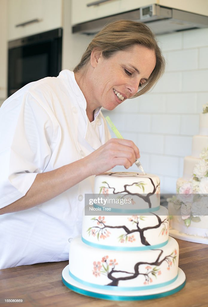 A cake maker decorating a cake
