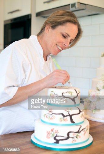 Cake Decorating Stockists Uk : A Cake Maker Decorating A Cake Stock Photo Getty Images
