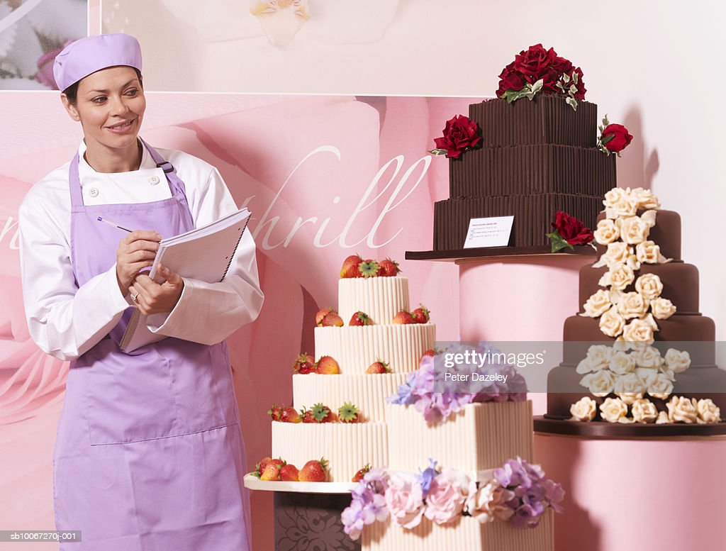 Cake maker in cake shop, holding notebook, smiling : Photo