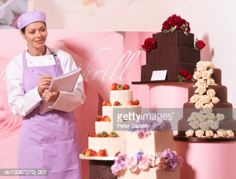 Cake maker in cake shop, holding notebook, smiling : Stock Photo