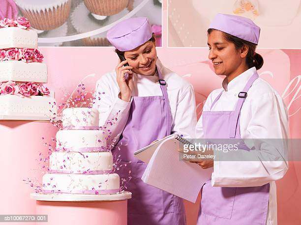 Cake makers in shop, one using mobile phone