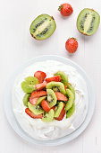 Meringue cake Pavlova with kiwi and strawberry, top view